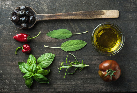 Vegetables and herbs on dark rustic wooden background  Greek black olives  fresh green sage  rosemary  basil herbs  oil  tomato