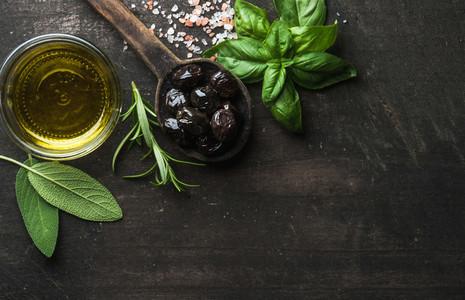 Greek black olives  fresh herbs and oil on dark rustic wooden background
