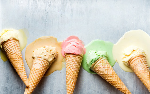 Colorful ice cream cones of different flavors Melting scoops Top view  steel metal background