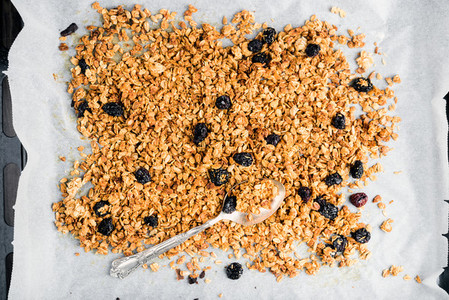 Homemade oat  cherry and coconut granola over baking paper with spoon