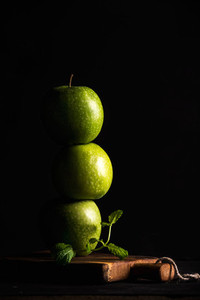 Green apples making stack or tower with branch of fresh mint on black background
