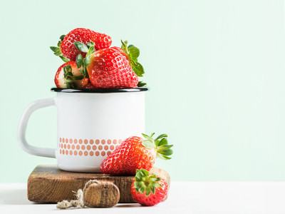 Fresh ripe red strawberries in country style enamel mug on rustic wooden board pastel light mint background