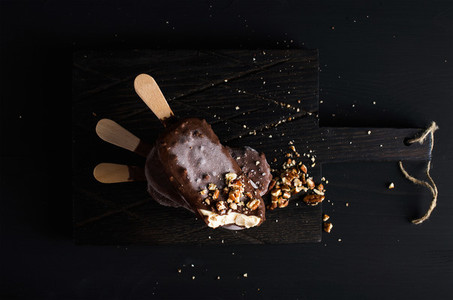 Chocolate dipped popsicles with chipped nuts on dark wooden board over black background