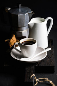 Cup of hot espresso  creamer with milk  cantucci and moka coffee pot on a rustic wooden board