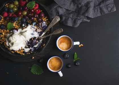 Healthy breakfast  Oat granola crumble with fresh berries  seeds and ice cream in iron skillet pan on dark wooden board over black backdrop