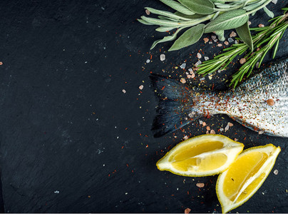 Tail of fresh raw Dorado or sea bream fish on black slate stone board with spices  herbs  lemon and salt