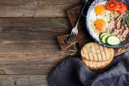 Breakfast set  Pan of fried eggs with bacon  fresh tomato  cucumber  sage and bread on rustic serving board over wooden background
