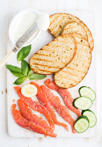 Ingredients for healthy sandwich  Grilled bread slices  smoked salmon  cottage cheese  cucumber nd basil on white wooden board