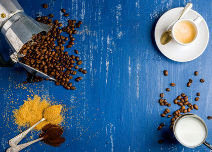 Espresso cup  cream  arabika beans in moka pot  brown sugar and ground coffee on wooden blue painted background