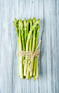Green fresh asparagus on light painted wooden background