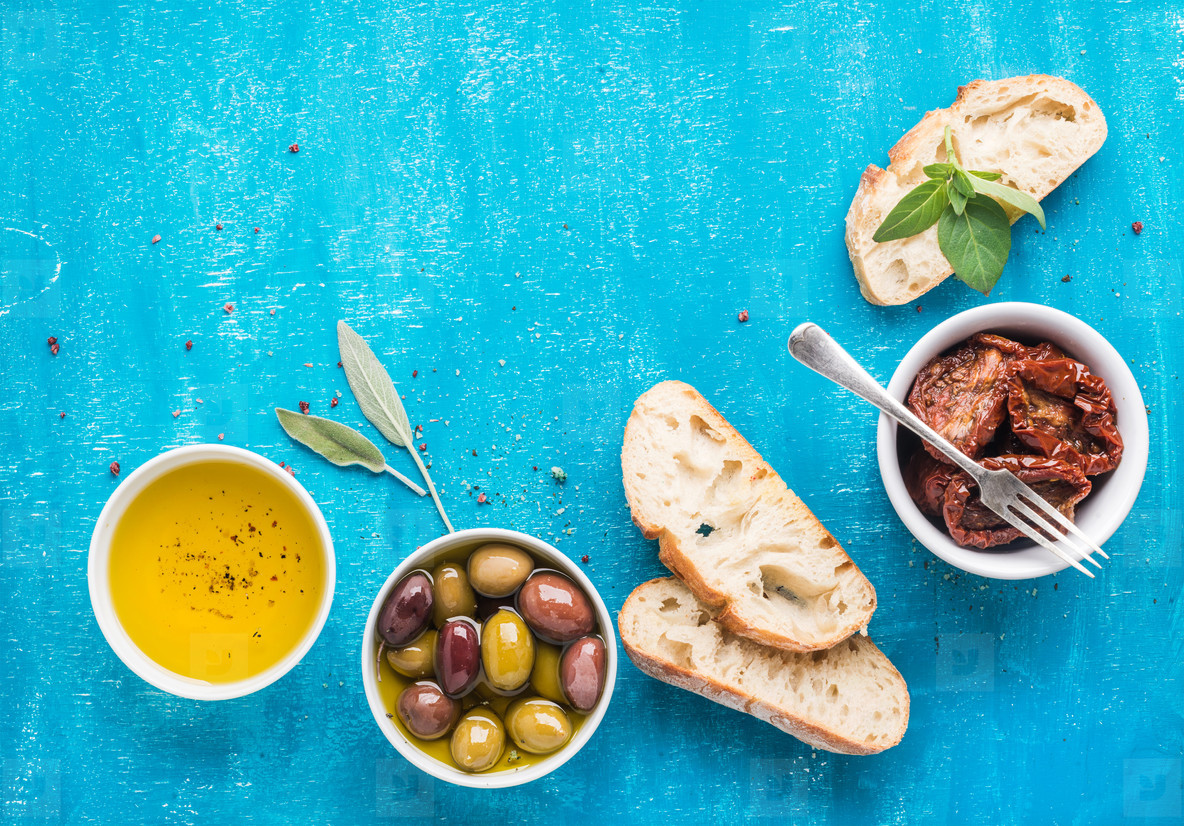 Mediterranean snacks set  Olives  oil  sun dried tomatoes  herbs and sliced ciabatta bread on over blue painted background