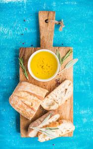 Mediterranean snacks set  Olive oil  herbs and sliced ciabatta bread on rustic wooden board