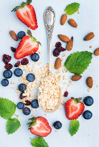 Healthy breakfast ingredients Oatmeal berries almond and mint leaves on painted blue wooden background