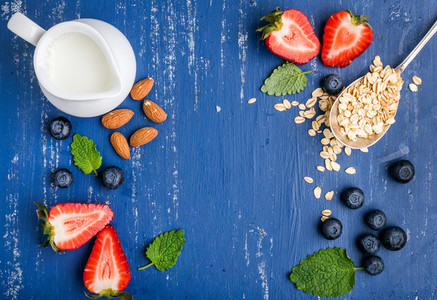 Healthy breakfast ingredients food frame  Oatmeal  milk in creamer  berries  almond and mint on painted blue wooden background