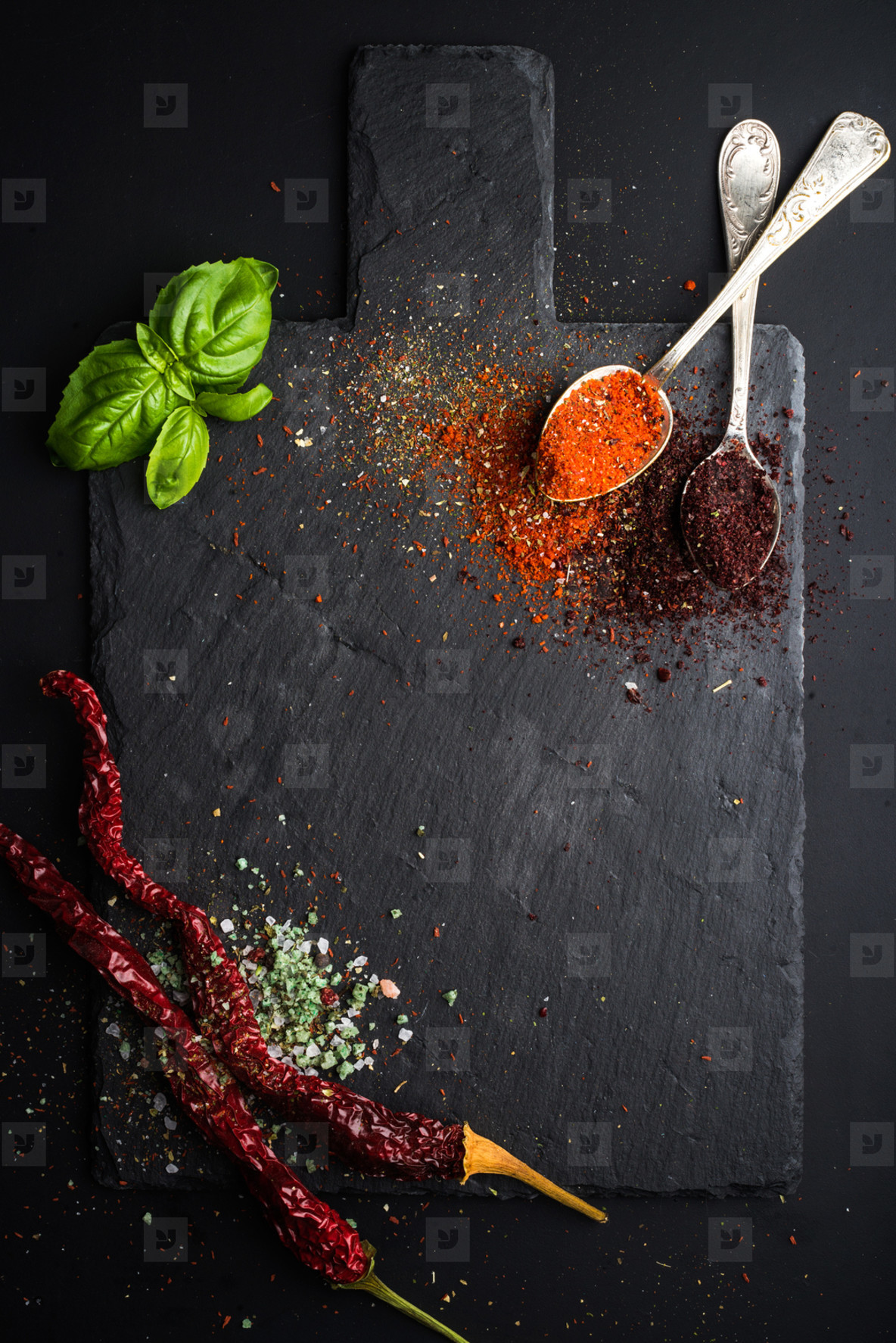 Herbs and spices on black slate stone board over dark background