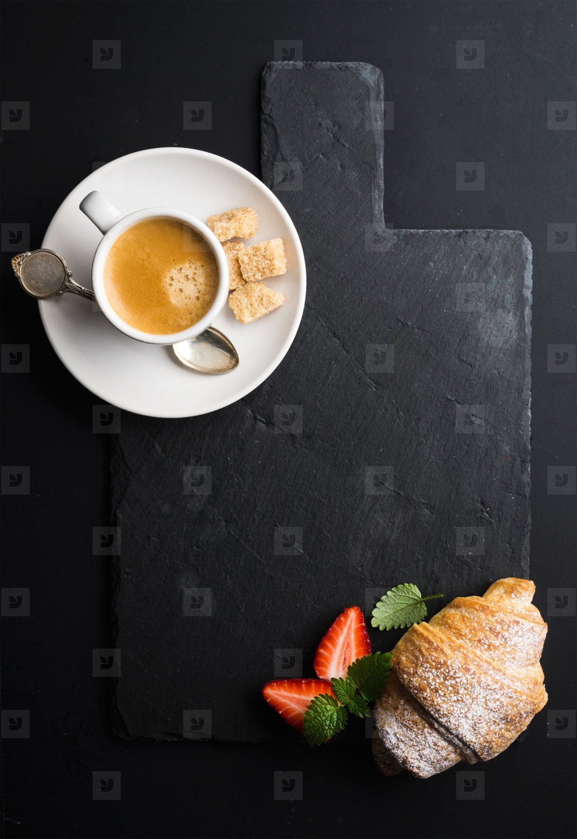 Espresso coffee cup and croissant with fresh strawberries on black  slate stone board over dark background
