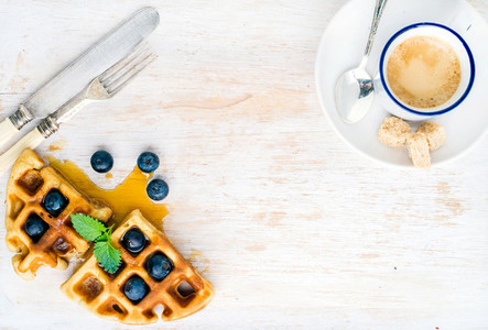 Espresso coffee cup soft belgian waffles with fresh blueberries and marple syrup on white painted wooden board over light blue background