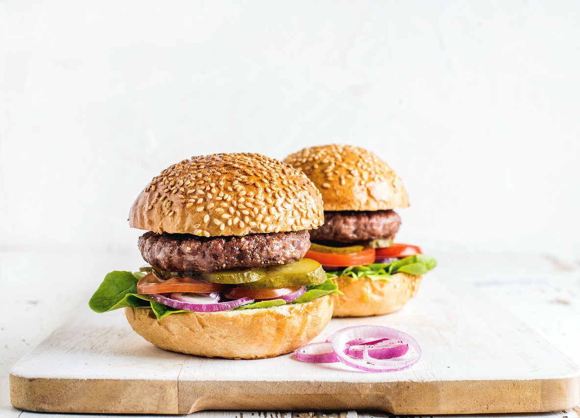 Fresh homemade burgers on wooden serving board with onion rings