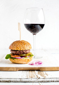 Fresh homemade burger on wooden serving board with onion rings and glass of red wine