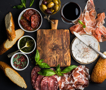 Wine snack set with empty wooden board in center  Glass of red  meat selection  mediterranean olives  sun dried tomatoes  baguette slices  camembert cheese and spices on black background