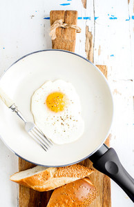 Fried egg with spice and bread slices in white ceramic frying pan on wooden board