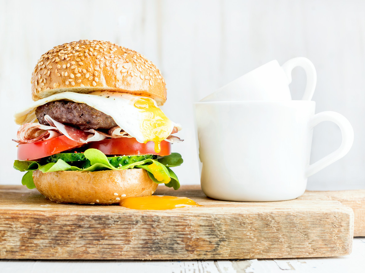 Breakfast set  Homemade beef burger with fried egg  vegetables  onion rings and coffee cups on wooden board