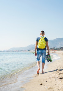 Young hipster man walking along the sea shore and beach barefoot with his sneakers in hand