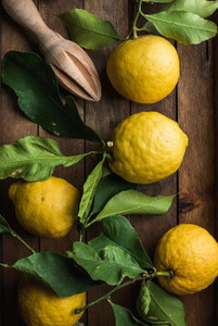 Fresh lemons with leaves in rustic wooden box