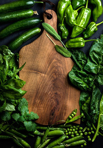 Fresh raw green ingredients for healthy cooking or salad making with dark wooden cutting baoard in center  top view  copy space