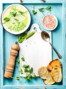 Light summer green pea cream soup in bowl with sprouts  bread toasts and spices  Top view  copy space