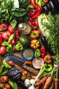 Fresh raw vegetable ingredients for healthy cooking or salad making  top view  Olive oil in bottle  spices and knife