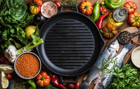 Ingredients for cooking healthy dinner  Raw uncooked seabass fish with vegetables  grains  herbs and spices over rustic wooden background  cast iron pan in center