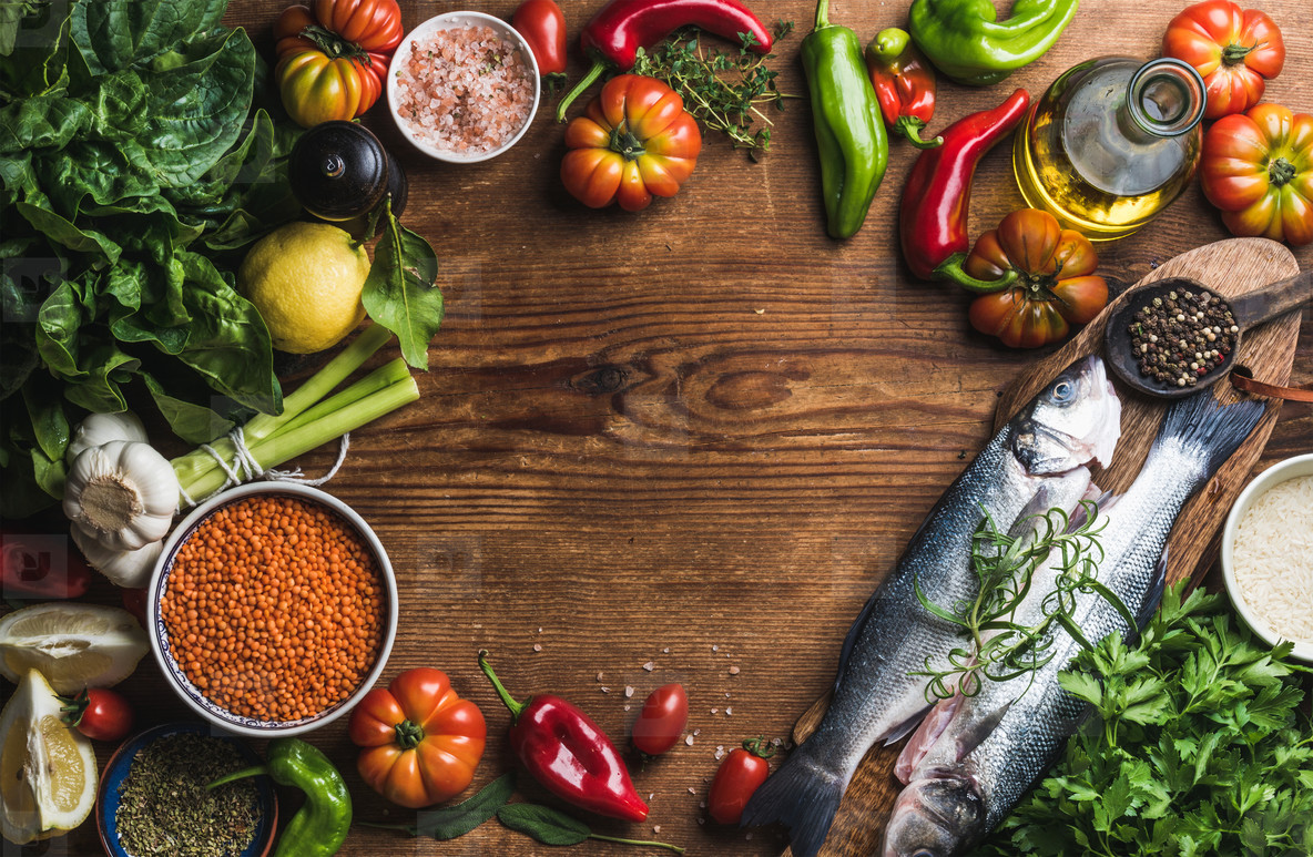 Ingredients for cooking healthy dinner  Raw uncooked seabass fish with vegetables  grains  herbs and spices over rustic wooden background