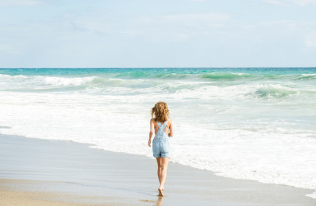Young woman in blue denim jumpsuit walking to the sea