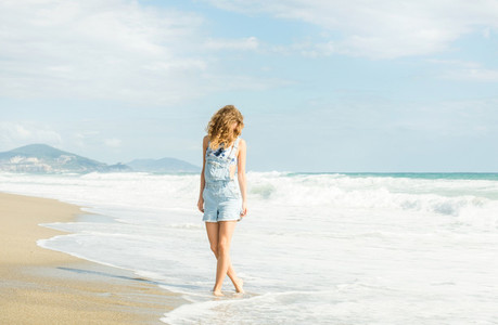 Young woman in blue denim jumpsuit walking along beach and the stormy ocean on sunny day