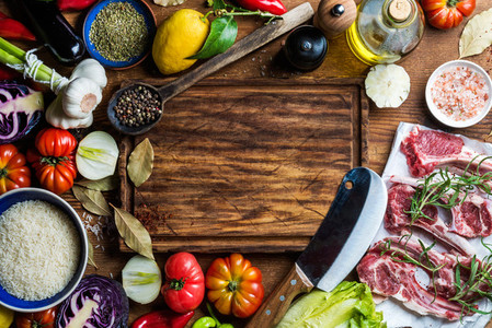 Ingredients for cooking healthy meat dinner  Raw uncooked lamb chops with vegetables  rice  herbs and spices over rustic wooden background  dark chopping board in center