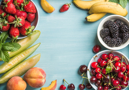 Healthy summer fruit variety  Sweet cherries  strawberries  blackberries  peaches  bananas  melon slices and mint leaves on blue backdrop