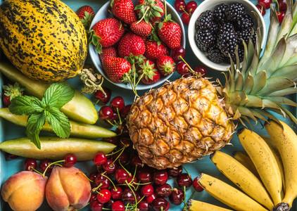 Healthy summer fruit variety  Sweet cherries  strawberries  blackberries  peaches  bananas  melon slices and mint leaves