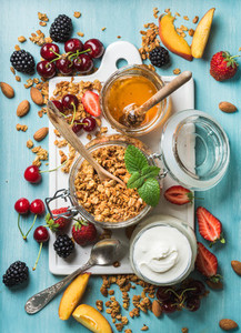Healthy breakfast ingredients  Oat granola in open glass jar  yogurt  fruit  berries  honey and mint on blue background