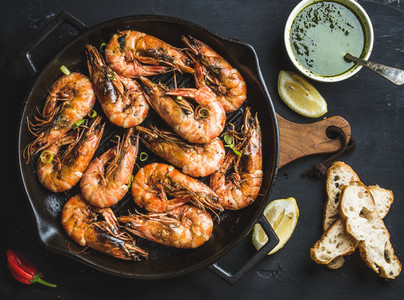 Roasted tiger prawns in iron grilling pan with fresh leek lemon bread and pesto sauce over black background