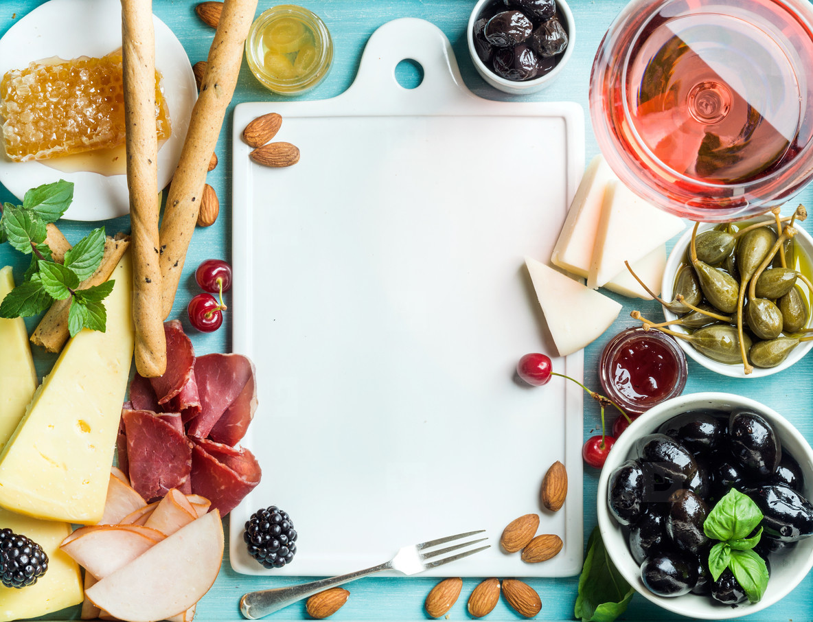 Summer wine snack set  Glass of rose  meat  cheese  olives  honey  bread sticks  nuts  capers and berries with white ceramic board in center  blue wooden background