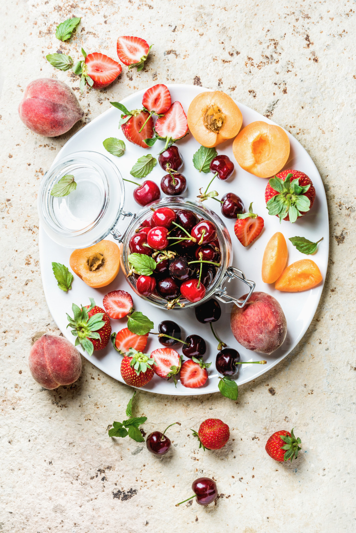 Healthy summer fruit variety  Sweet cherries  strawberries  peaches  apricots and mint leaves on white ceramic serving plate over light concrete background