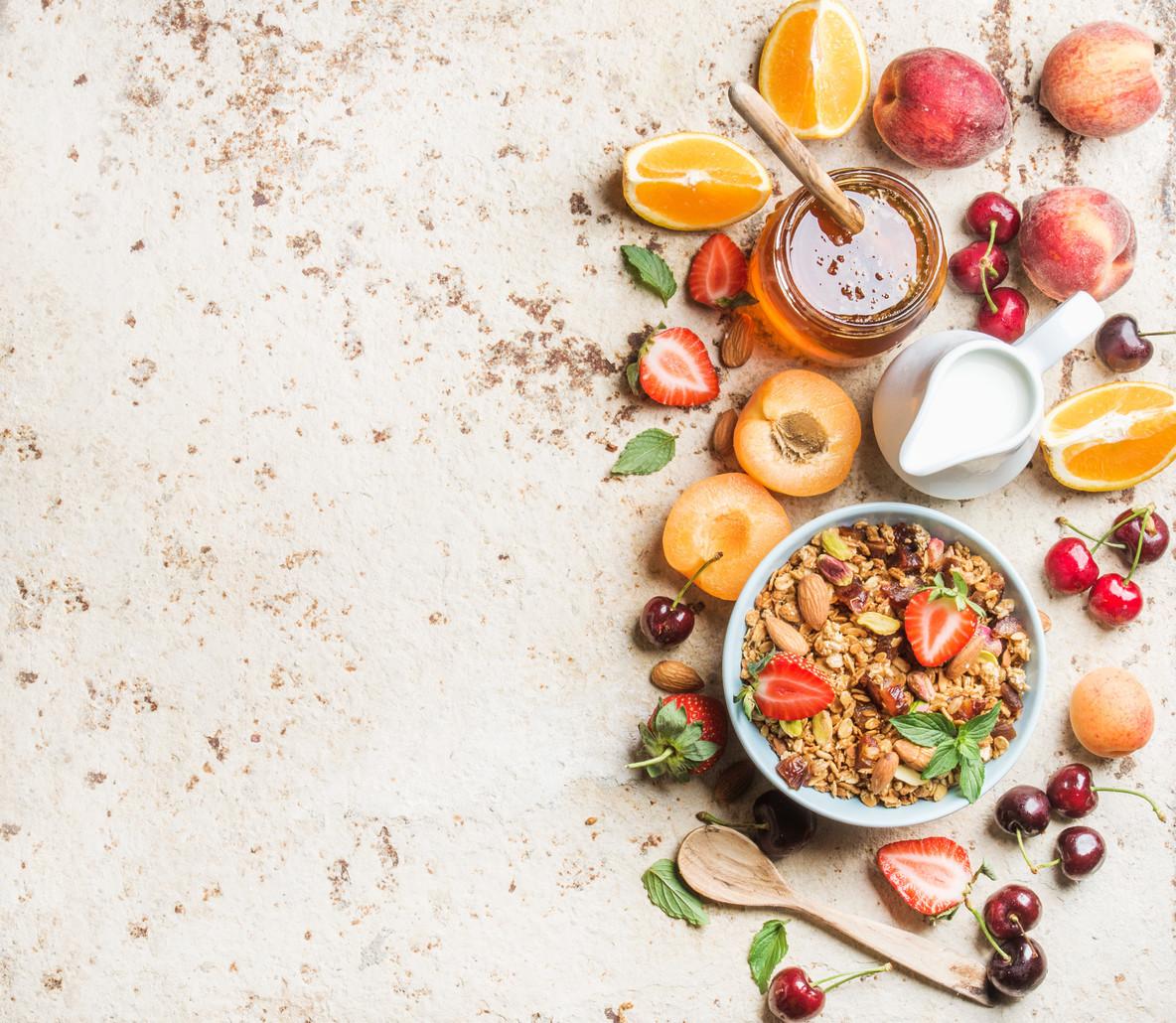 Healthy breakfast ingredients  Bowl of oat granola with milk  fresh fruit  berries and honey