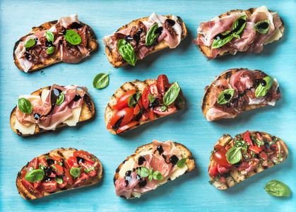 Brushetta snacks for wine  Variety of small sandwiches on turquoise blue backdrop