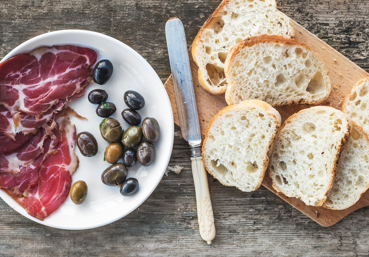 Smoked meat or prosciutto and olives on a white plate  vintage knife  baguette slices over rough wood background