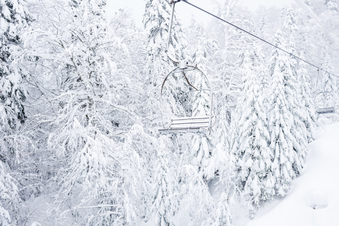 Old cable lift with no passengers going across coniferous forest in  Kolasin 1450  mountain ski resort near the town of Kolasin  Montenegro after a heavy snowfall