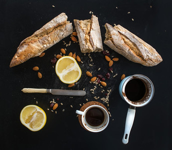 Rustic breakfast set of french baguette broken into pieces  grapefruit  sunflower seeds  almonds and coffee on dark