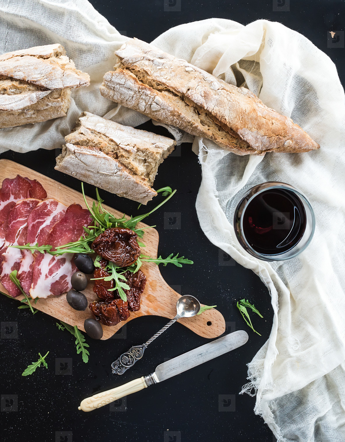 Wine appetizer set  vintage dinnerware  french baguette broken into pieces  dried tomatoes  olives  smoked meat and arugula on rustic wooden board over dark background