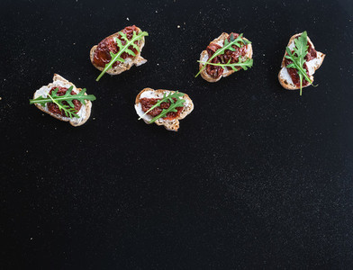 Bruschettas with dried tomatoes  arugula and smoked meat over a
