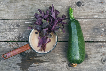 A marrow and a bunch of basil in an old metal scoop